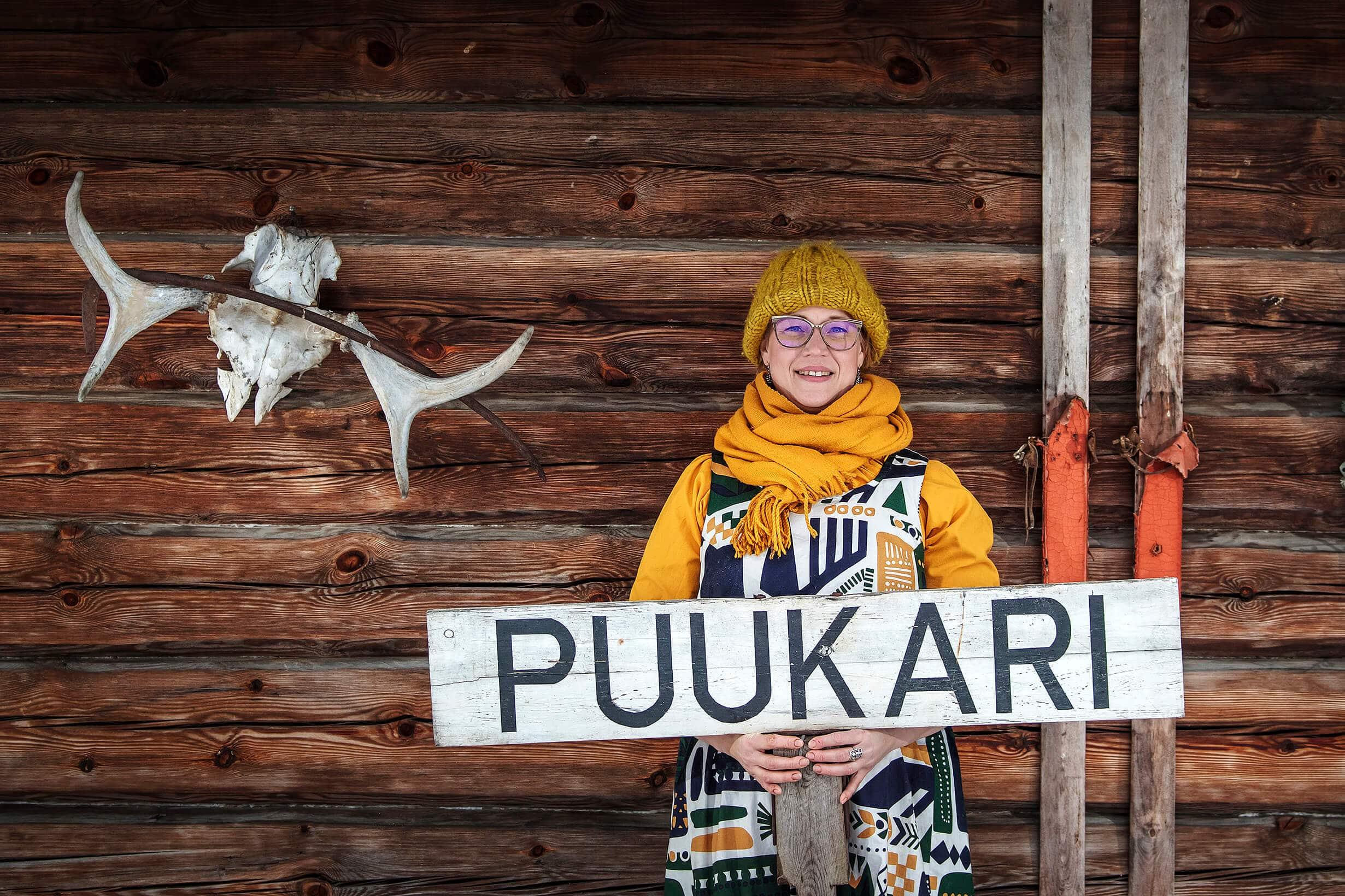 Puukarin Pysäkki Anni seinustalla kyltin kanssa